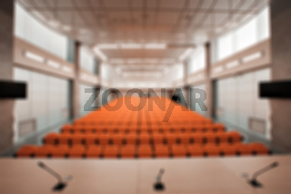 Abstract blur Rostrum with microphone and computer in conference hall. Orange color