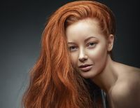 Beauty Girl Portrait. Healthy Long Curly Red Hair.