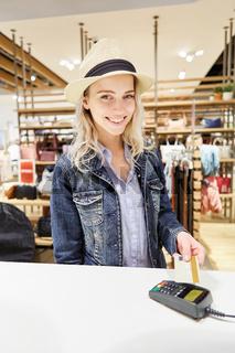 Frau hält Kreditkarte über das Kartenlesegerät