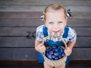Little child girl with basket full of plums