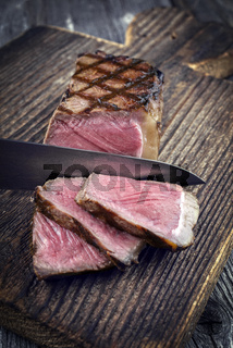Barbecue New York Strip Steak on old Wooden Board