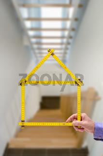 Meterstab symbolisch als Modellhaus im Treppenhaus