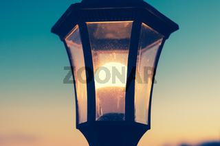 Close-up of a street lamp glowing