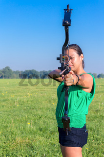 Woman aiming with bow and arrow in nature