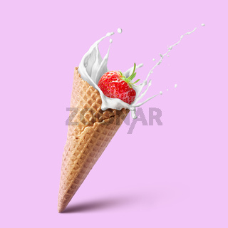 Ice cream waffle cone with milk splash and strawberry isolated on pink