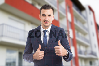 Handome young real estate agent showing like thumb up gestures