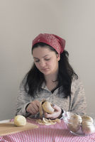Brunette woman peeling potatoes