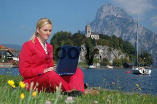 Blonde Frau im Anzug, am Ufer des Traunsees arbeitet im Freien am Laptop