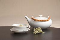 A teapot and a teacup nicely arranged on a table