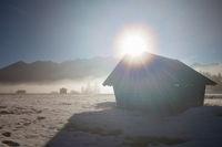 sunshine over wooden hut in Alps