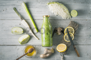 Glass bottle with smoothie with different ingredient on the white wooden table horizontal