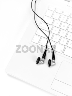 A laptop computer with a set of earphones isolaterd against a white background