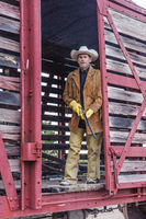 Cowboy with a gun stands in the open doorway of an old-fashioned Train Rail Car