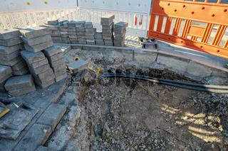 Baustelle mit Steinen und Kabel mit Drainage aus Kies