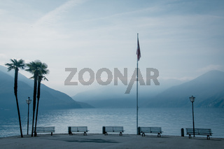 Coast of lago maggiore with view on the foggy lake