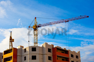 Two cranes and unfinished house construction