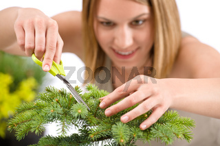 Gardening - woman trimming spruce tree, focus on scissors