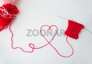 knitting needles and thread in heart shape