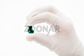 fingers in white glove holds dioptase crystal