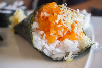 Cone shaped salmon temaki sushi over white plate