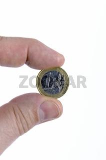1 Euro Muenze, zwischen den Fingern einer Hand