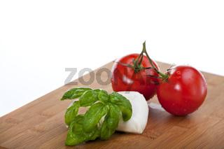 tomatoes, mozzarella and basil while making insalada caprese