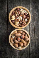 Different types of nuts in wooden bowl.