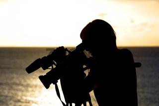 Silhouette einer jungen Frau mit professioneller Videokamera
