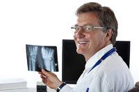 Älterer sympathischer Röntgenfacharzt betrachtet Röntgenbild.