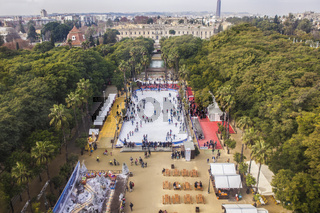 Aerial view from the top of ferris wheel with crowded ice and cityscape of Seville