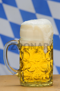 Maßkrug in Bayern auf dem Oktoberfest mit bayerischer Fahne