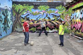 Ein serbischer, deutscher und thailändischer Junge spielen gemeinsam auf einem Bolzplatz, Köln, Nordrhein-Westfalen, Deutschland, Europa