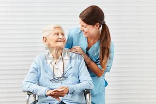 Lächelnde Seniorin im Rollstuhl und Pflegerin