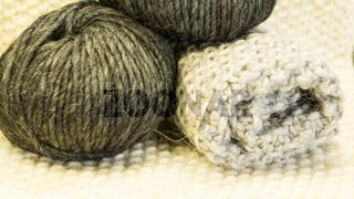 Strickstück mit Wolle im Knaeul in Grau und Anthrazit auf getricktem Untergrund