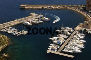Weisse Motorjacht fährt in den Yachthafen Fontvielle am Mittelmeer