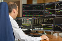 Rear view of stock trader analyzing data at multiple computer screens.