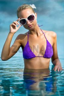 Beautiful girl relaxing in shiny blue water