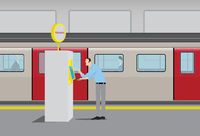 Young Man Using Automatic Ticket Machine at Subway Station