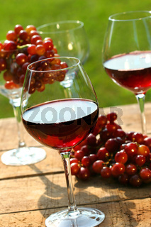 Three glasses of red wine with grapes on rustic table