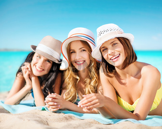 group of happy women in hats sunbathing on beach