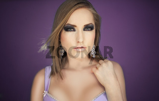 Sexy glamour girl in violet bra posing on purple  background