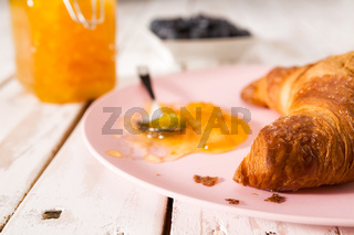 Closeup of croissant and jam on a pink plate