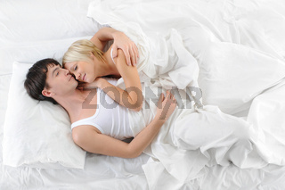Happy family lying in bed