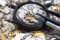 tools on open watch on heap of clock spare parts