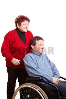 Frau schiebt älteren Mann im Rollstuhl