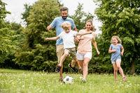 Junge spielt und läuft mit dem Fußball