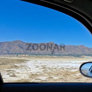 View from the window of a car to the semi-desert in Central Turkey with a salty depression in the foreground and bare rocks on the horizon.