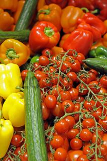 bunter Gemuesekorb mit roten Paprika, Strauchtomaten, gruenen Gurken, gelben Paprika