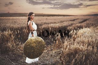 Brunette wearing in dress like greece style holding shield.