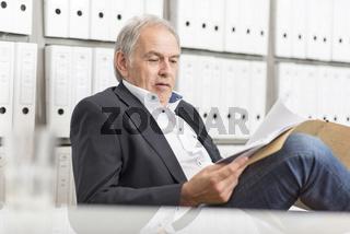 Älterer Mann im Anzug vor einer  Regalwand mit Dokumenten Ordner